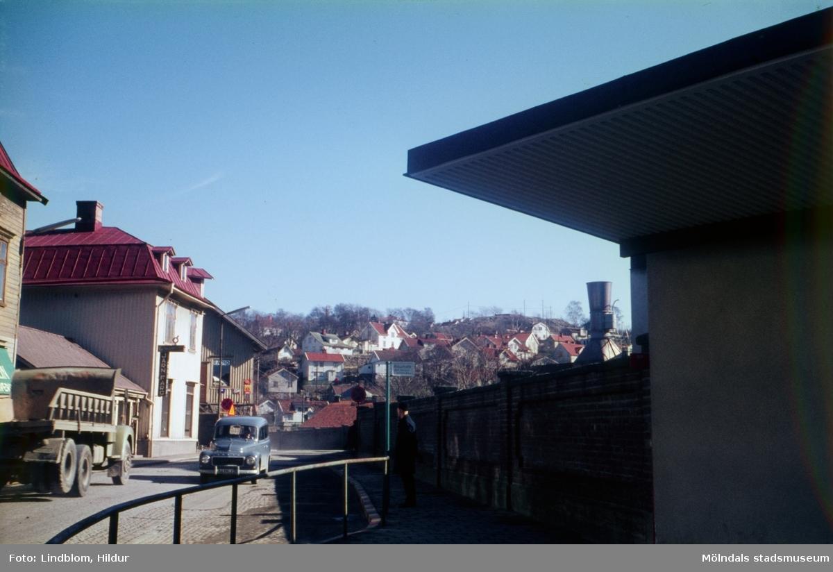 Vy från Papyrus port mot byggnader vid Kvarnbygatan i Mölndal, 1960-tal. På höger sida av gatan ses Papyrus mur. På vänster sida ses bakom lastbilen taket till C.J. .Johanssons Järnhandel med adress Kvarnbygatan 27. Det vita huset är även det nr 27 och bakom det ses del av gaveln till gamla rådstugan med adress Kvarnbygatan 29.  För mer information om bilden se under tilläggsinformation.