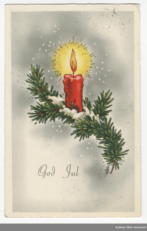Vit ram på grå skuggad botten. Grangren med tänt rött stearinljus och lite snö. Under motivet står God Jul med svarta bokstäver.