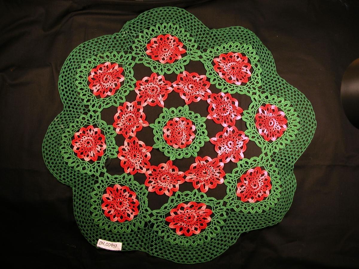 """Raud rose med grønt rundt i midten. 8 raude roser rundt. 8 raude roser med grønt rundt, der ei av """"hempene"""" på det grøne er bøtt/forsterka med mørk blå tråd. Grøn kant i rutemønster ytst."""