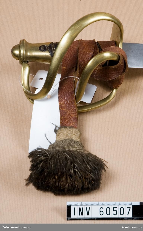 Grupp D II. Handrem till pallasch m/1807 för kyrassiär, Ryssland. Handremmen är av brunt läder med tofs av vitt ullgran.