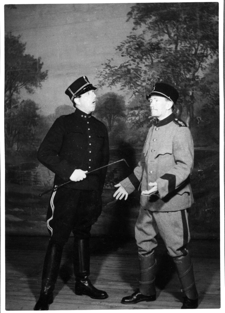 Revy på A 6. Två man på scen i uniform.