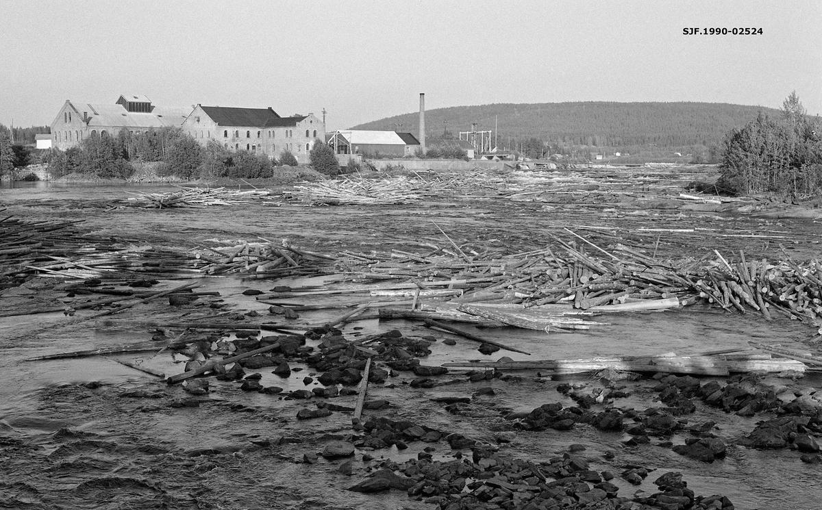 Sammenvaset fløtingstømmer i Glomma på ettersommeren i 1959.  Dette var en tørkesommer, noe som bidro til at vannføringa i elva etter hvert ble uvanlig lav, slik at tømmeret strandet på grusører og bergflater i elveløpet, slik at det bygde seg opp digre tømmerhauger.  Sentralt i bildet ser vi produksjonsanlegget ved Funnefoss tresliperi, som ble etablert i 1874-75 av Anders Olai Haneborg.  Nærheten til fossen, som ghav energi, vassdraget, som var transportåre for tømmer, og jernbanen, som brakte det ferdige produktet til markedet, var de sentrale lokaliseringsfaktorene.  Haneborg startet med to hoprisontale slipeapparater, og utvidet med ytterligere ett i slutten av 1880-åra.  I 1918, i forkant av den store krisa som rammet trelast- og papirbransjen etter 1. verdenskrig, gikk Haneborg konkurs.  Sør-Odal kommune overtok fabrikken og skogene fra konkursboet, først og fremst fordi kommunene var interessert i å sikre seg fallrettighetene i Glomma.  Fabrikken ble utleid til et firma, som ville fortsette tremassefabrikasjonen.  Alt i 1919 brant imidlertid mye av anlegget ned til grunnen.  Fabrikken ble gjenreist under navnet A/S Nye Funnefoss Træsliberi, med produksjon i de teglsteinsbygningene vi ser på dette fotografiet.  Bedriften var i virksomhet fram til 1966, sju år etter at dette fotografiet ble tatt.