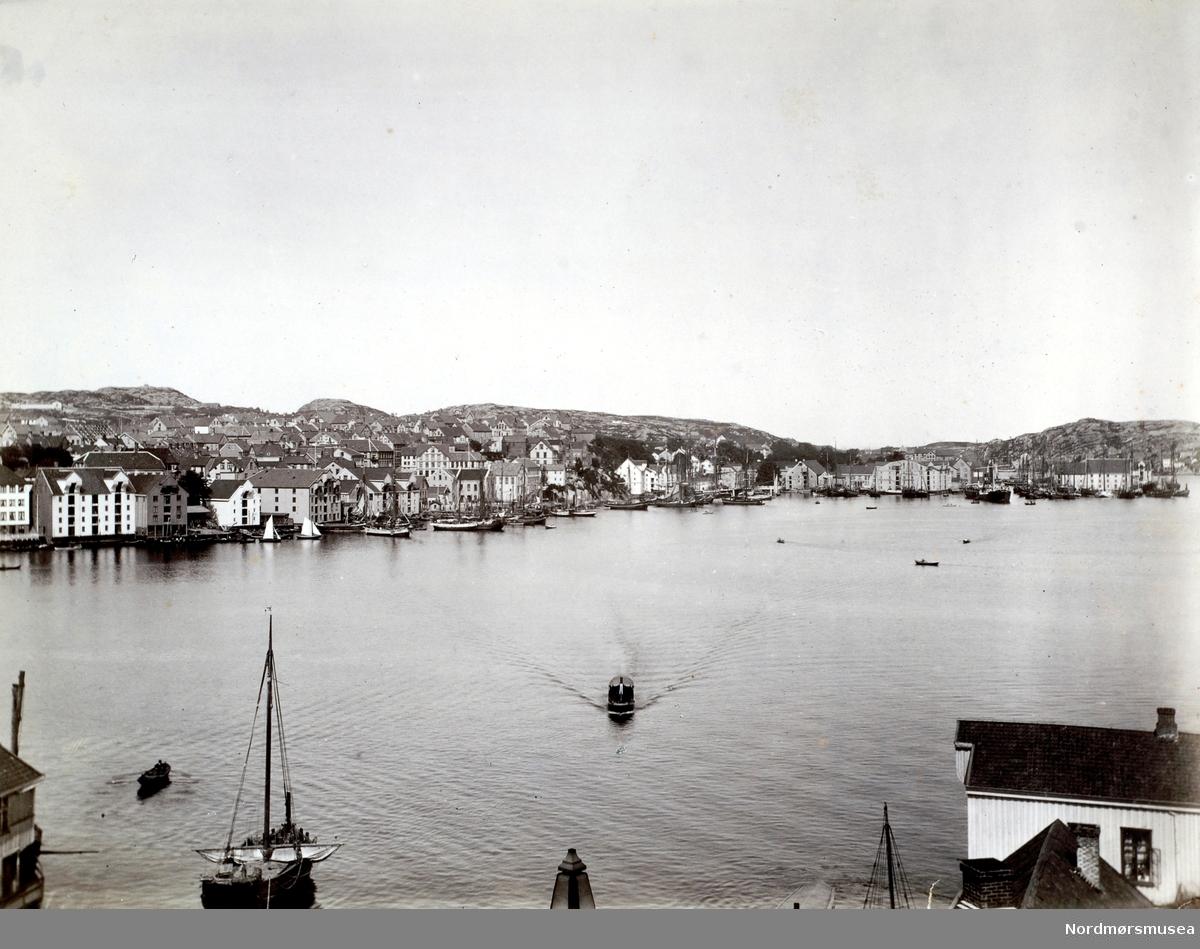Foto fra tatt fra Sagerbukta på Innlandet mot havnebassenget og Kirkelandet i Kristiansund på andre siden av havna. Bildet er trolig fra perioden rundt 1880 til 1890. Sundbåt. Fotograf er Johan K. Engvig. Fra Nordmøre Museums fotosamlinger.