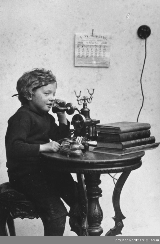 """Et foto av Ernst Ranheimsæter som sitter ved telefonen. Merk den """";åpne""""; typen telefon, og uttaket i veggen. Ellers så er det verdt å merke seg bøkene på det vesle bordet, samt kalenderen som henger på veggen. Bildet er gitt av Anita Ranheimsæter Reinert, så bildet er mest sannsynlig fotografert av Ole Olsen Ranheimsæter, som var en kjent fotograf i Kristiansund på denne tiden. Fra Nordmøre Museums fotosamlinger."""