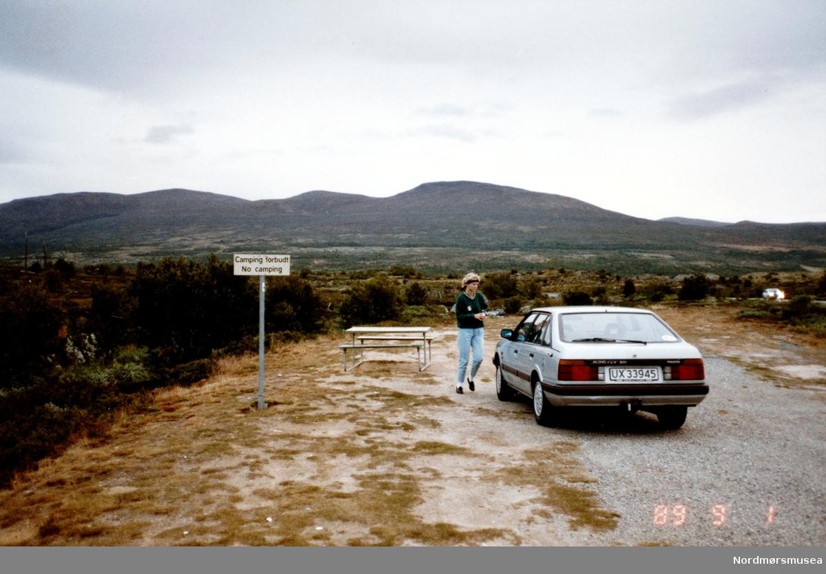 Foto av en bil med registreringsskilt UX 33945, her parkert på en rasteplass - muligens på Averøy kommune. Det er forøvrig ukjent hvem vi ser på bildet. Bildet er datert 1. september 1989. Fra Nordmøre museums fotosamlinger. Reg: EFR