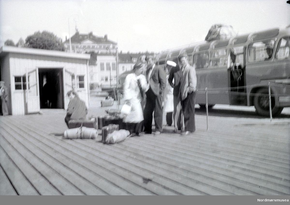 Bildet er tatt på kaia i Larvik, bussen skal sikkert ombord i Peter Wessel, Larvik-Fredrikshavnferjen. (Info: Svein-Erik Eriksen).  Busspassasjerer ved en buss. Etter bildet å dømme kan dette være T-6708 Volvo turbuss fra Batnfjord Auto. Karosseriet ble påbygd hos Bussbygg i Hovdenakken, og bussen ble levert i 1952. På 1950-tallet ble den brukt mye som turbuss i inn- og utland.  (se reg. nr. KMb-2008-024.N559 og KMb-2008-024.N563) Det er forøvrig ukjent hvem vi ser på bildet, samt hvor og når bildet er tatt. Russ? Solskinnsbuss Fra Ida Knudtzons fotosamling. Fra Nordmøre museums fotosamlinger.