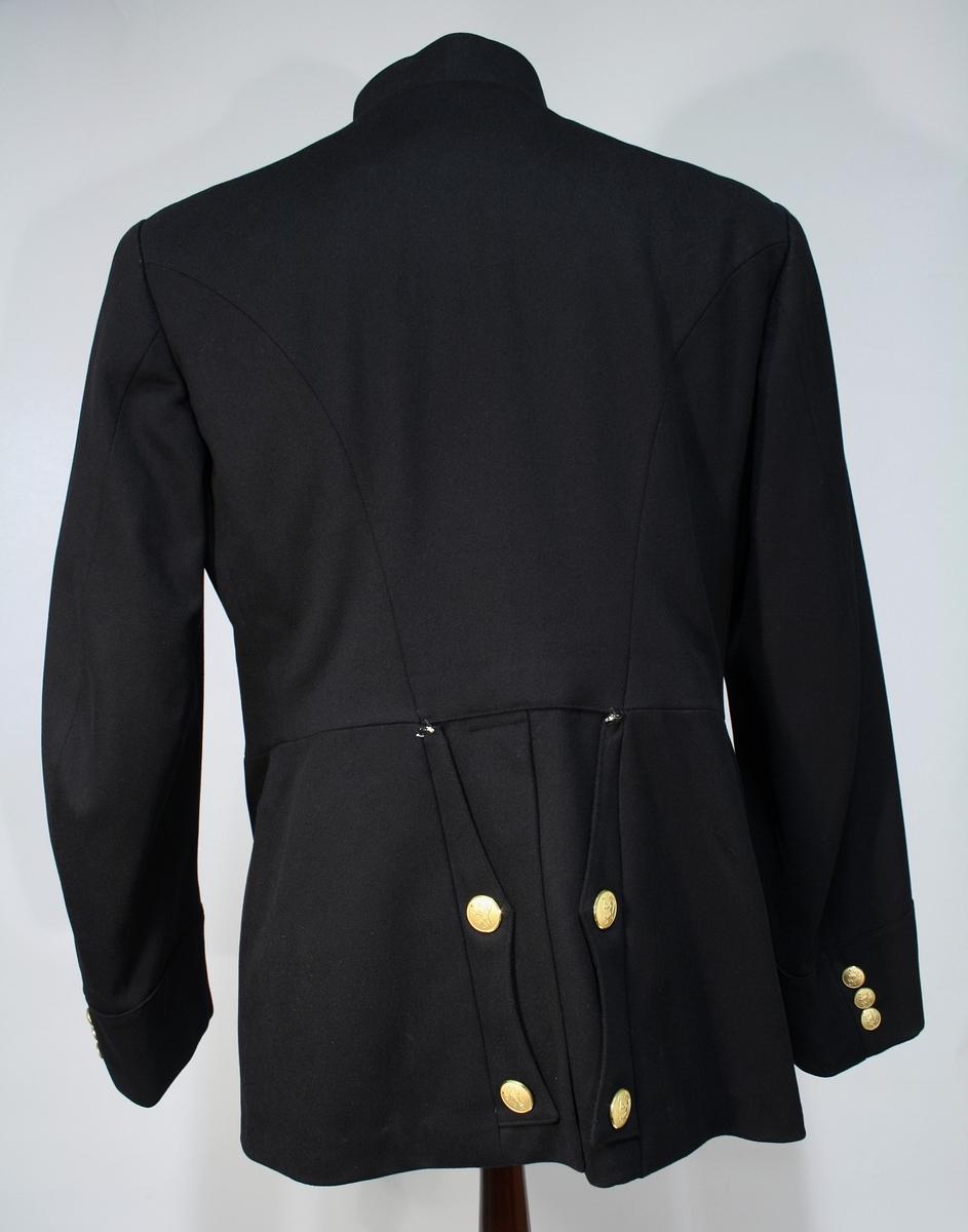 Mørkeblå uniformsjakke. Enkeltspent med syv forgylte knapper. Har kragedistinksjoner for politiembetsmenn. Splitt bak med seks riksløveknapper (mangler to), og tre riksløveknapper på hvert erme. Jakken er sydd tett til kroppen.