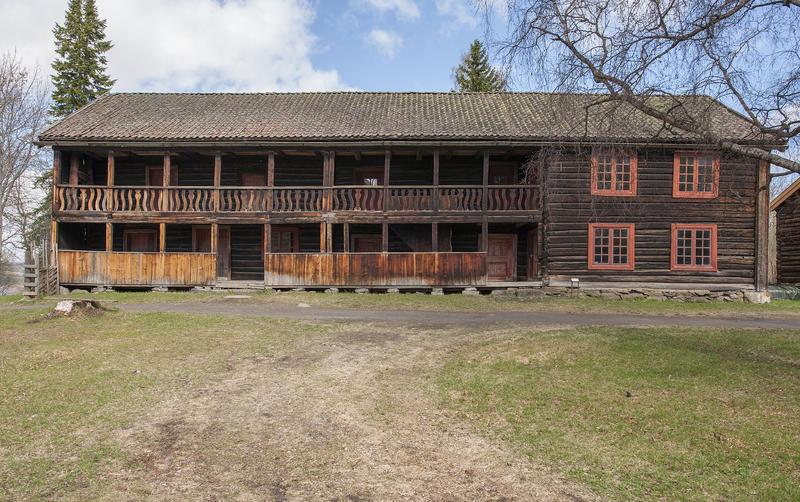 Hubredbygningen på Hedmarkstunet er en lang, brunlig tømmerbygning i to etasjer med svalgang langs hele langveggen.