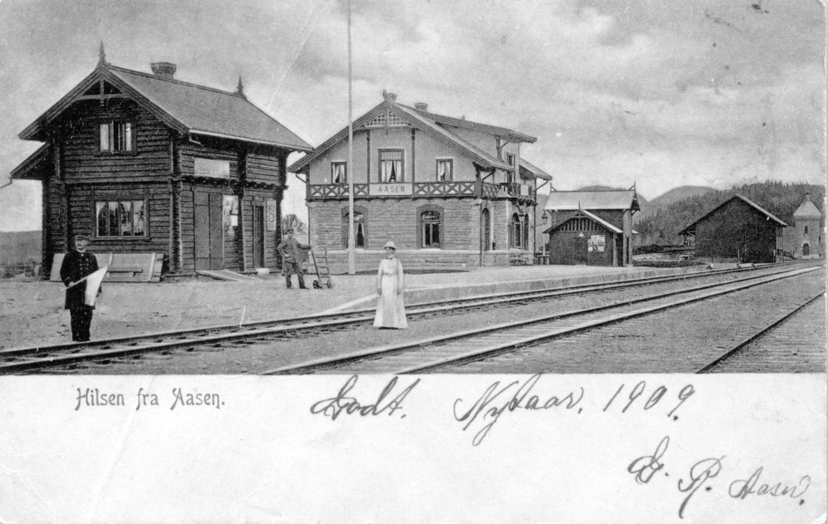 Åsen jernbanestasjon. Stasjonsmesteren og trolig hans ektefelle i forgrunnen, en stasjonsbetjent i bakgrunnen.