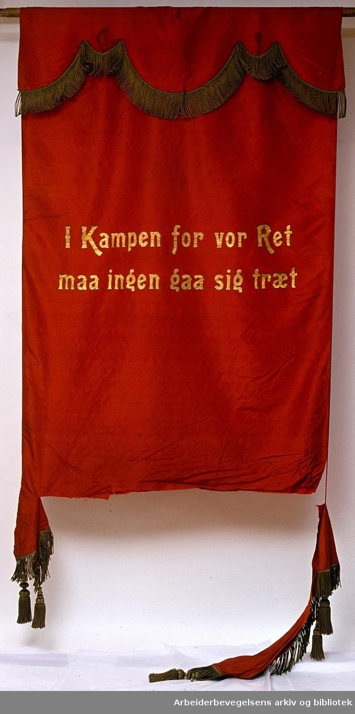 Smedenes fagforening.Stiftet 12. oktober 1883..Bakside..Fanetekst: I Kampen for vor Ret maa ingen gaa sig træt..