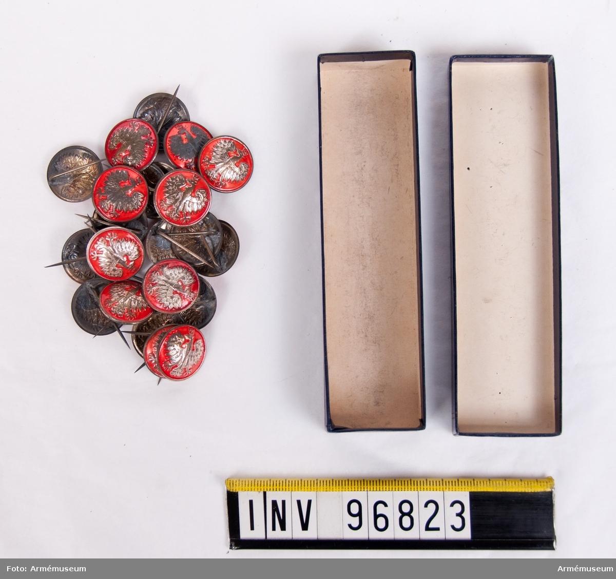 Pappask med 23 stycken metallnålar dekorerade med den polska örnen.