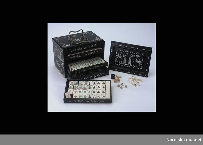 """Katalogkort: """"Mahjongspel med skrin av trä. 1800-1900-tal, Kina. Skrin i svartlackerat trä, med kinesiska figurinläggningar i  pärlemor. Framsidan består av en uppåt skjutbar lucka, löstagbar. Fem st. lådor vari ligger brickor, tärningar, stickor samt allt vad som hör till spelet  och allt i elfenben. På uppsidan dubbelhandtag av metall."""" Tillskrivet: """"Spelpjäserna i elfenben och bambu. På skjutluckans baksida röd rund stämpel m kinesiska tecken samt bl a. CHOWCHINA..."""""""