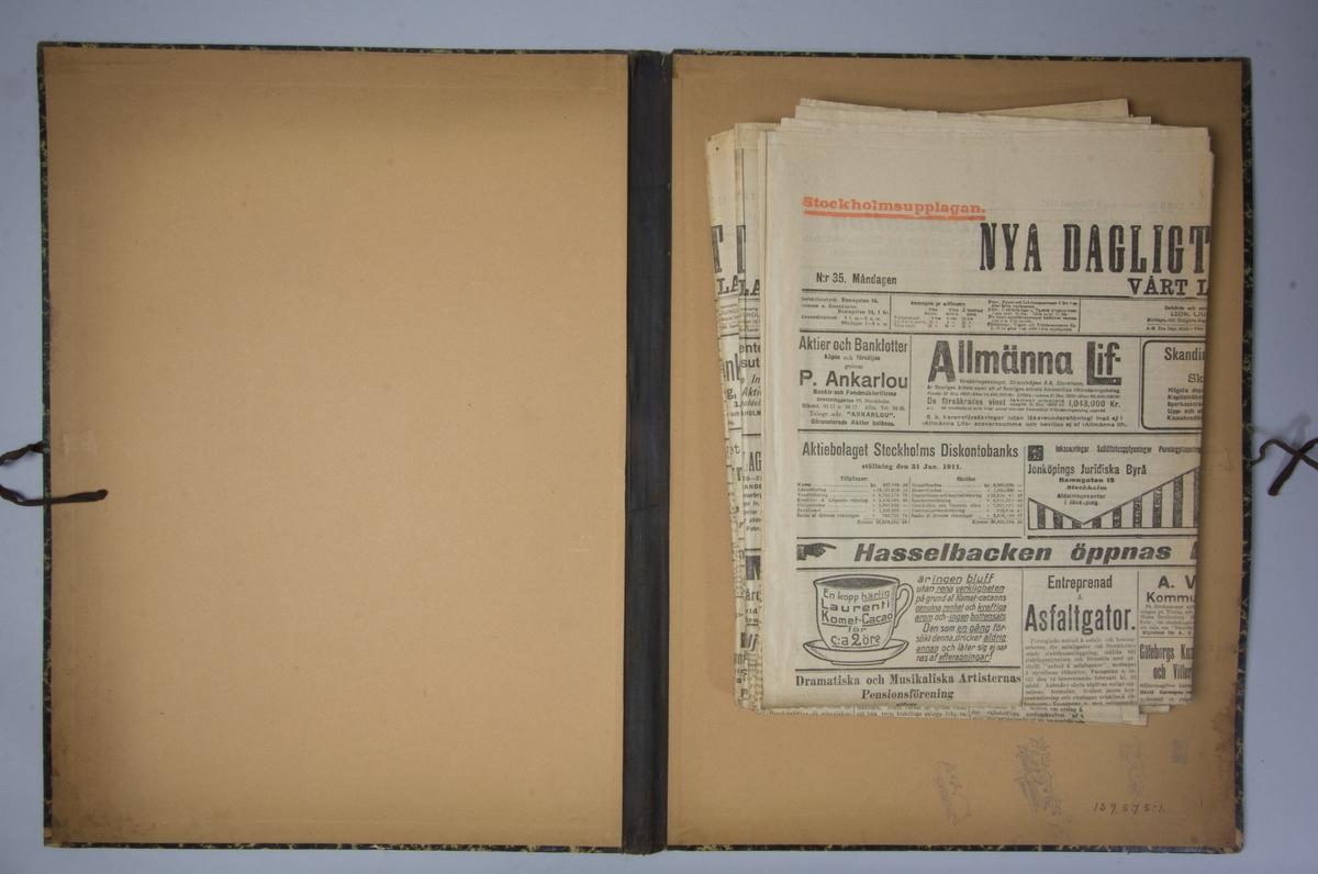 Portfölj av marmorerad papp. Sammanhållen med knytband. Rygg av svart linne. Innehåller enbart flera exemplar av Nya Dagligt Allehanda från 1911.