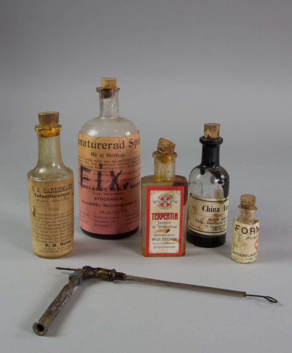 Tavelfernissa, 5 glasflaskor, klart glas, samt en fixerspruta av metall. Rester av innehåll i samtliga flaskor.