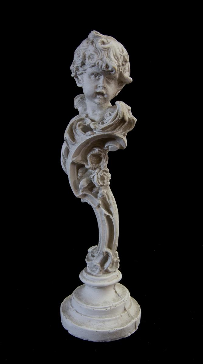 Studiemodell av gips föreställande ett barnhuvud. Huvudet är placerat på ett volutformat stöd. Rund sockel.