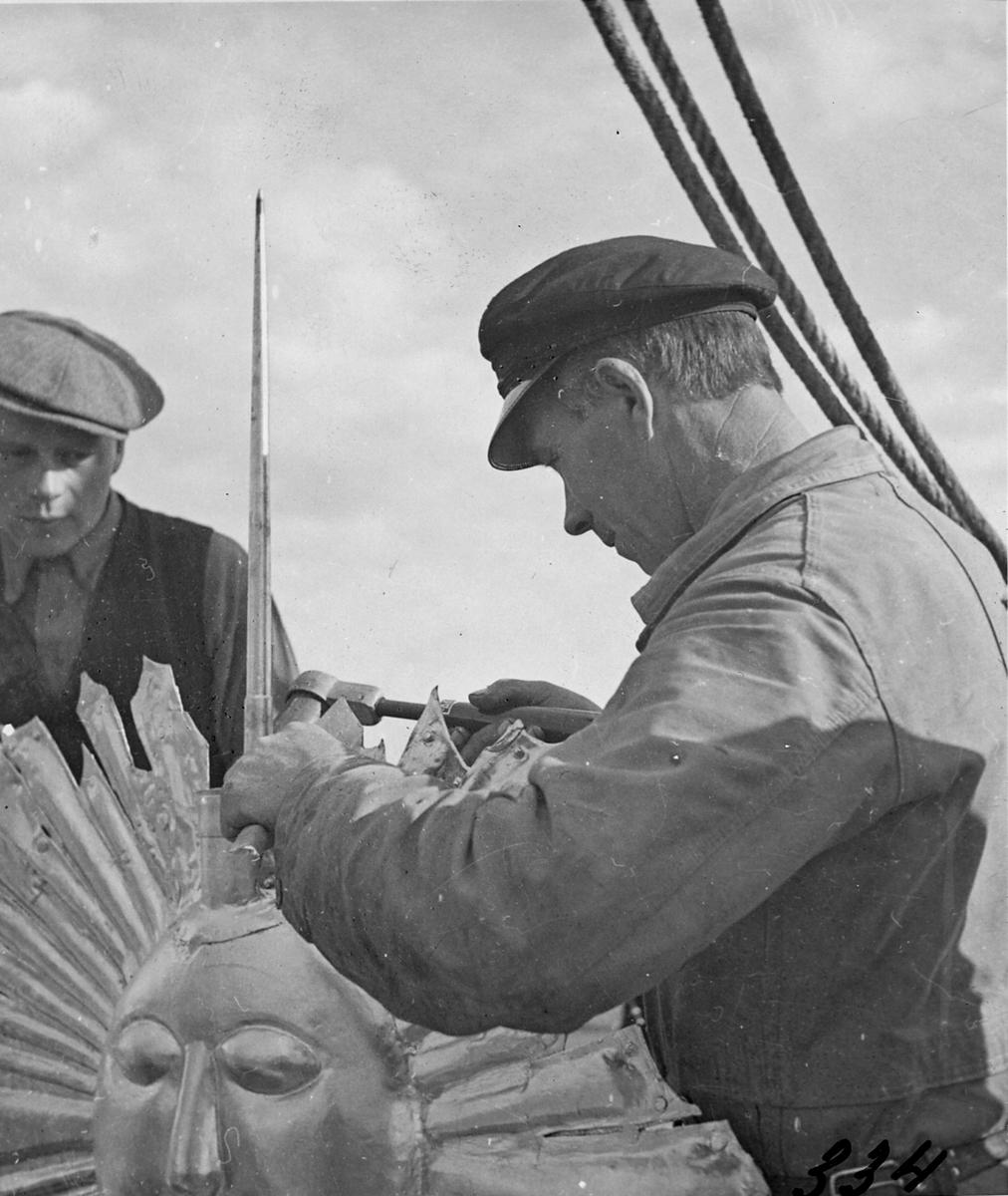 Plåtmästare E. Birath monterar åskledare till kyrktornet 1935.