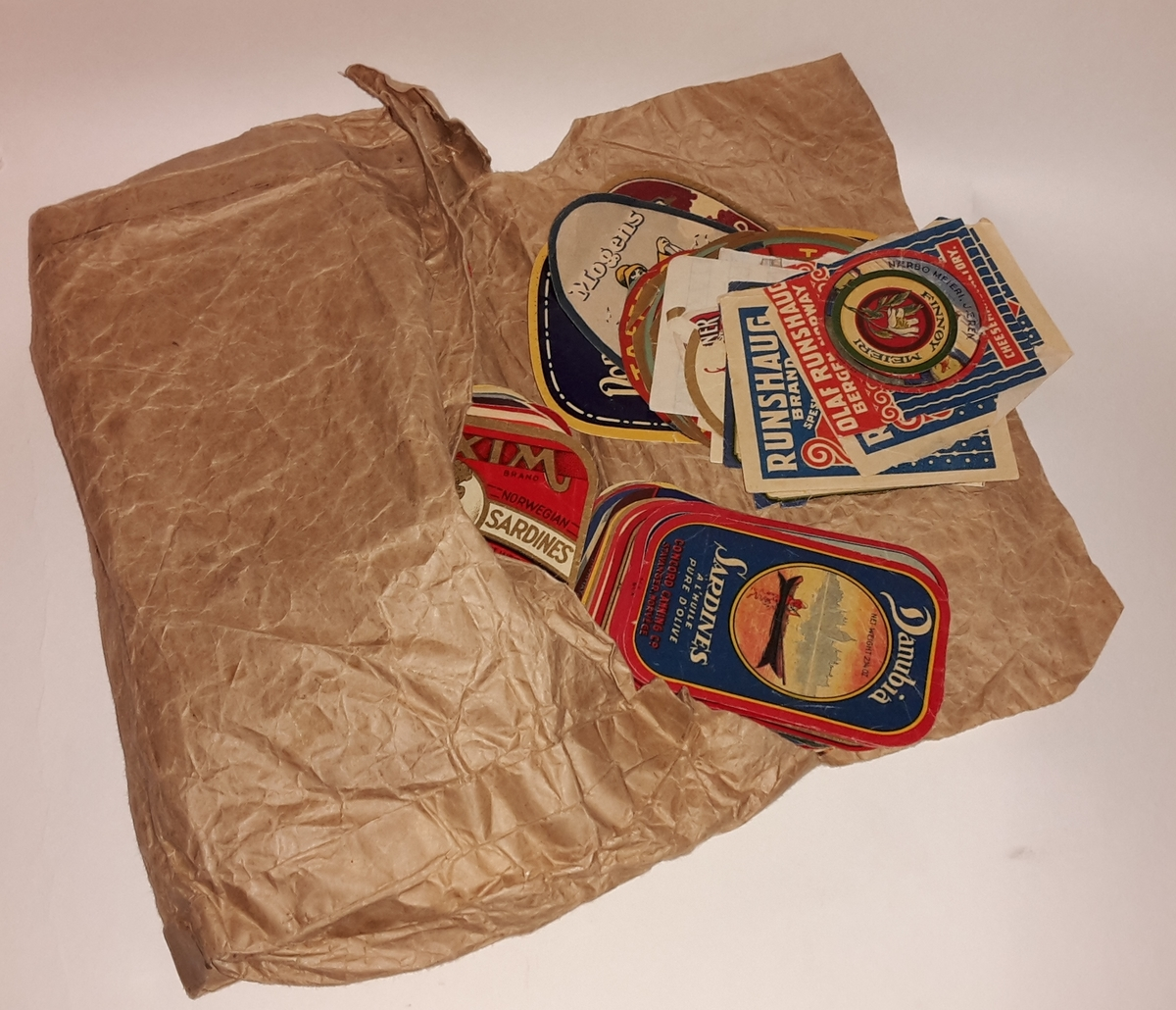 Iddisane ligg i papirpose laga av gråpapir, limt med limband i papir.