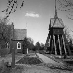 Foto av en (mindre) kyrka  med klockstapel till höger. Tuta
