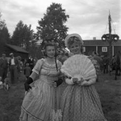 Foto av en midsommarstång med två kvinnor med utklädsel till