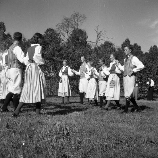 Foto av flera kvinnor och män iklädda folkdräkter som dansar.