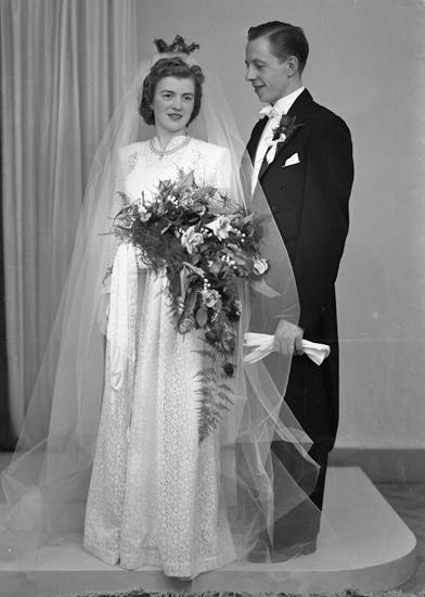 6f1d57d4fe38 Bruden är klädd i vit, mönstrad brudklänning med slöja och myrtenkrona.  Brudgummen bär frack.