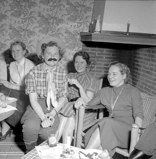 Fyra kvinnor sitter vid en öppen spis, en av kvinnorna har utklädesplagg på sig.
