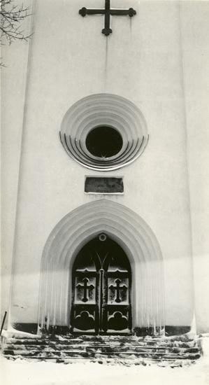 Foto av kyrka med kyrkport och trappa. Vinterbild.