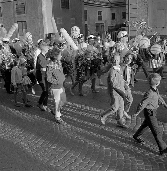Studenterna, tredje d. 1960. Studenterna m.fl. marscherar uppför Storgatan mot Stortorget. I bakgrundensyns bakgården m.m. till dåv. G. Bergstrands fastighet.