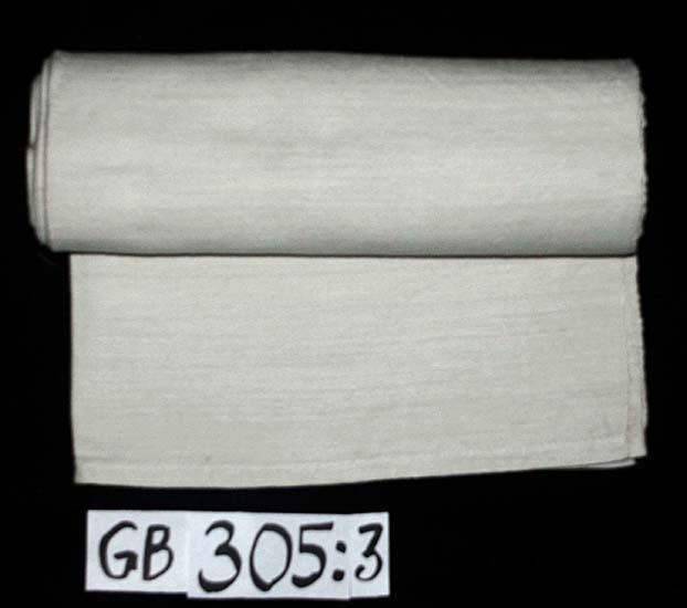 Lakan. Handvävt. Kvalitet: halvlinne, bomull i varp, lin i inslag. Teknik: liksidig kypert. Vävbredd:  67 cm, 2 längder hopsydda. Fållar: 2,5 resp. 1 cm breda, handfållade. Inskrivet i huvudkatalogen 1996-1997. Funktion: Underlakan