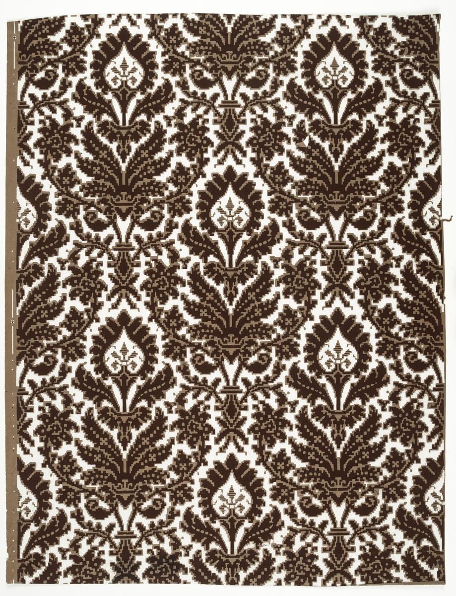 Symmetriskt textilmönster med renässanskaraktär, mörkbrunt mot vit fond. Obestruken botten av gråbrunt genomfärgat papper, bottenfärgen utsparad i mönstret. Två tryckfärger. Tillverkad av Norrköpings tapetfabrik. IB