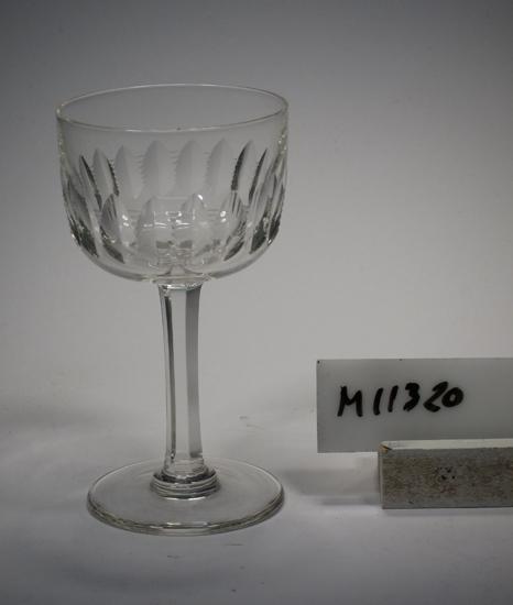 """Brännvinsglas tillhörande servis """"Ulle"""". Möjligen tillverkat 1904. Se """"Ulle"""" slipben, nr. 1619-1629, pl. XXII i fotoalbum. Slipad dekor i form av parallella skär med hack emellan. Facetterat ben. Ofärgat klarglas. Ovan angivna mått avser övre diameter. Fotdiameter: 50 mm. Rymd: 6 cl. Inskrivet i huvudkatalogen 1942. Funktion: Brännvinsglas"""
