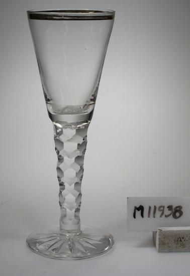 Glas (R.193). Beskrivning: Dekor bestående av slipade skär, fjällslipning samt guldkant runt mynningen. Färg: Ofärgat klarglas. Mått: Diameter ovan avser glasets fotdiameter. Inskrivet i huvudkatalogen 1942. Funktion: Servisglas