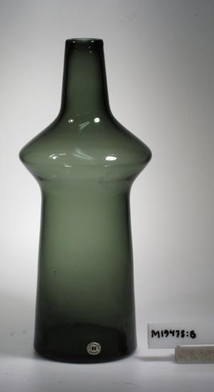 """Blomglas """"Adam"""". Art.nr: A 184. Konstnär: Tom Möller. Beskrivning: Konisk form med en utbuktning på övre delen som övergår till en avsmalnande hals. Färg: Rökgrågrönt klarglas. Mått: Ovan angivna diameter avser vasens bottendiameter. Signerad, samt märkt med lapp med text och en oval etikett i guld och blått med text. Se """"Signering, märkning"""" 1, 2 och 3ovan. Inskrivet i huvudkatalogen 1968. Funktion: Blomglas"""
