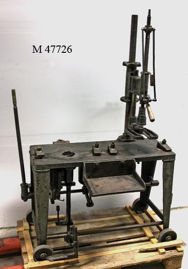 Sug och blåsmaskin, bestående av ett bord i gjutjärn,  på vars vänstra sida man placerade ämnesformen (se  ex M 24366). I denna sögs ämnet ut genom att dra i  spaken längst ut till vänster. Ämnet, som i detta läga  var uppochner, vändes rätt och lyftes sedan med hjälp  av ämnesformtången (se ex M 47721) som höll hylsan  med gängor över till färdigformen. I denna blåstes istället  glaset ut. Färdigformen var placerad till höger på bordet,  under en hög hävarm, som är ställbar genom en gängad  stång. Gammalt reg.kort anger att det finns fyra formar till maski- nen, men ej vilka formar det rör sig om. Dock, ämnesform  M 24366 passar perfekt i de gamla slitmärkena, vilket till- sammans med maskinens ålder och utseende gör att den  troligen kan tillskrivas Alvesta glasbruk. Inventerat 2007-01-18. Inskriven i huvudkatalogen 1996. Funktion: Användes till att tillverka glasflaskor och -burkar