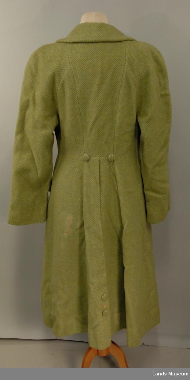 Grønn vinterkåpe. Den har grått silkefor.