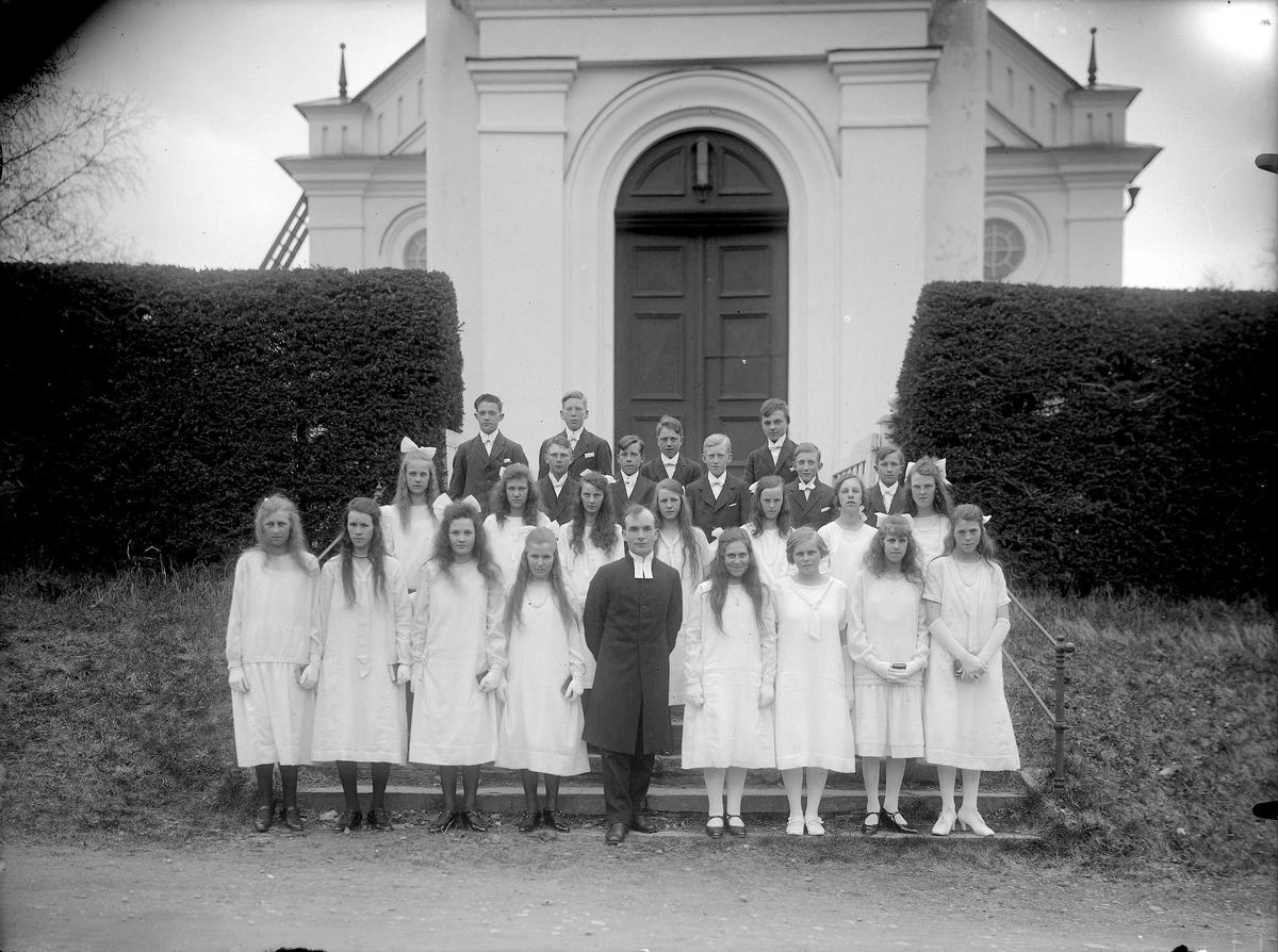 Gruppfoto av konfirmander 1926 framför kyrkan med Komminister Berglund.
