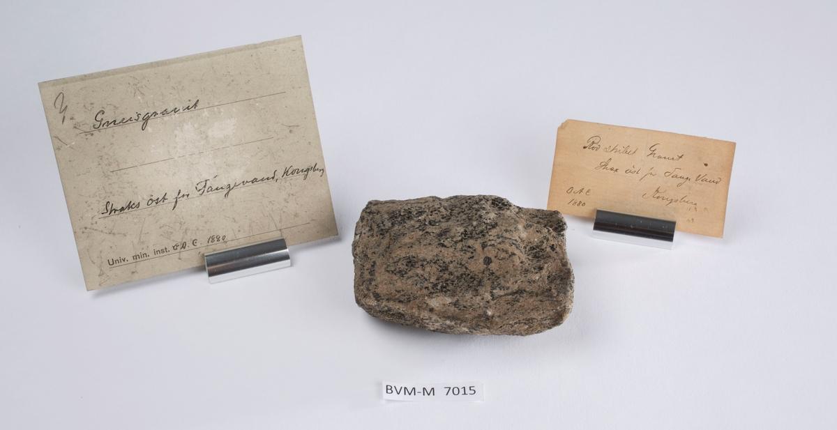 To etiketter i eske:  Etikett 1: Rødstribet Granit Strax øst for Tange Vand Kongsberg OAC 1880  Etikett 2: Gneisgranit Straks øst for Tangevand, Kongsberg O.A.C. 1880.