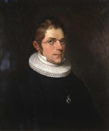Portrett av Nicolai Wergeland. Kort hår, briller, presteklole og prestekrave. En orden. (Foto/Photo)