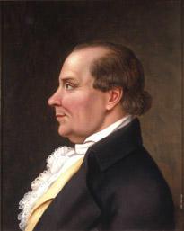 Portrett av Peder J. Cloumann. Profil. Mørk drakt, hvit skjorte med kalvekryss, lys gul vest.