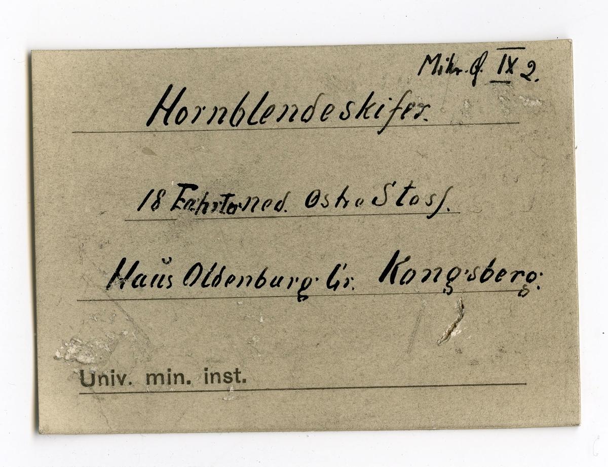 To etiketter i eske: Etikett 1: Indlagte er fra Hausoldenburgs Østre Side 18 fahrter ned  Etikett 2: Min. f IX 2. Hornblendeskifer 18 Fahrter ned. Østre Stoss Haus Oldenburg Gr. Kongsberg.