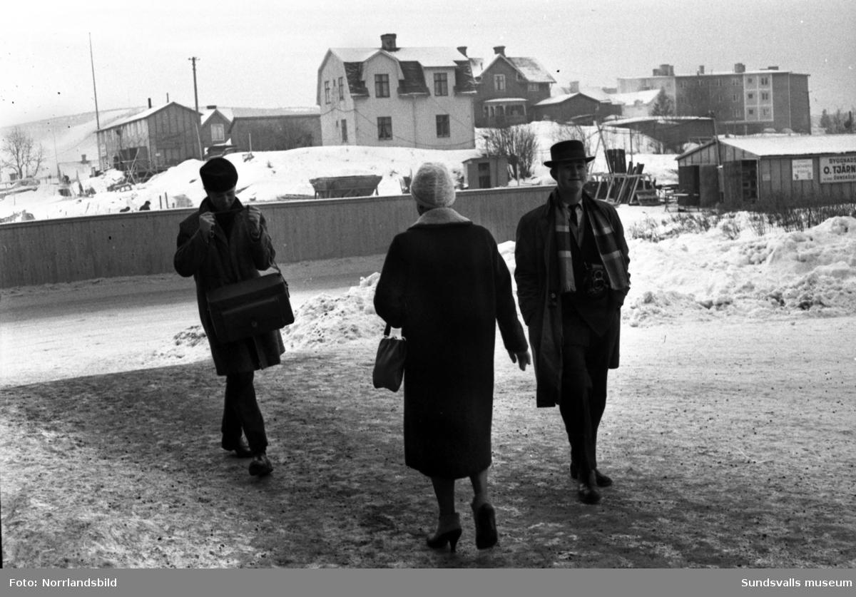 Vy fotograferad söderut från Folkets hus i Skönsberg. Tre personer i förgrunden, på andra sidan Medborgargatan pågår markarbeten för höghusbygget, på Gilleberget till höger finns både gammal och nyare bebyggelse och i bakgrunden till vänster skymtar slalombacken på Södra berget.