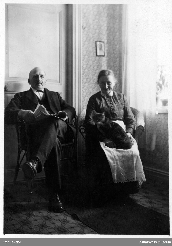 Hemma hos familjen Hydén på Skepparegatan 12, Norrmalm. På bild 1 ses snickaremästare Gustaf Hydén och frun, stadsbarnmorskan Anna Hydén med katt. På bild 2 ses döttrarna Rut, Anna och Elin Hydén.