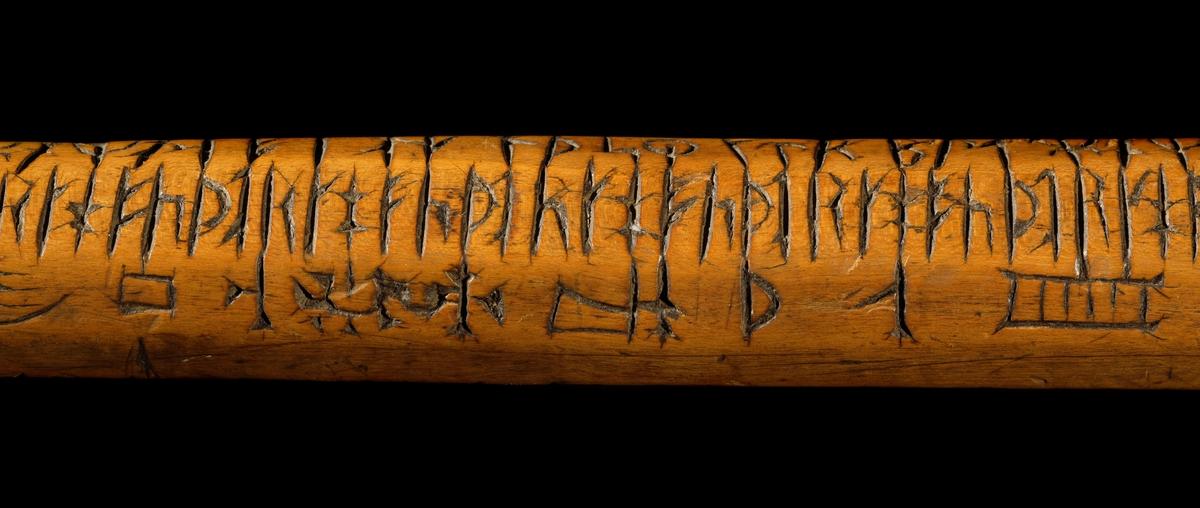 Kalenderstav i form av en åttkantig, stavformad runkalender. Av trä med snidat handtag. Doppsko av järn med pik inslagen i änden. Denna stav har fått symbolbilder inskurna. Osäker datering, ej initialer eller bomärke.