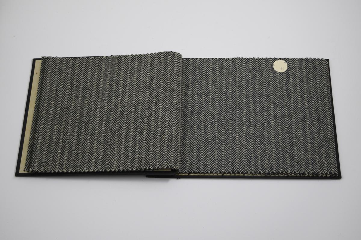 """Prøvebok med 4 prøver. Middels tykke stoff med fiskebensmønster og striper - mønsteret er tilnærmet likt på forsiden og baksiden av stoffet. Stoffene ligger brettet dobbelt i boken. Stoffene er merket med en rund papirlapp, festet til stoffet med metallstifter, hvor nummer er påført for hånd. Innskriften på innsiden av forsideomslaget viser at alle stoffene har kvaliteten """"Ola"""".   Stoff nr.: Ola/94, Ola/95, Ola/96, Ola/97."""