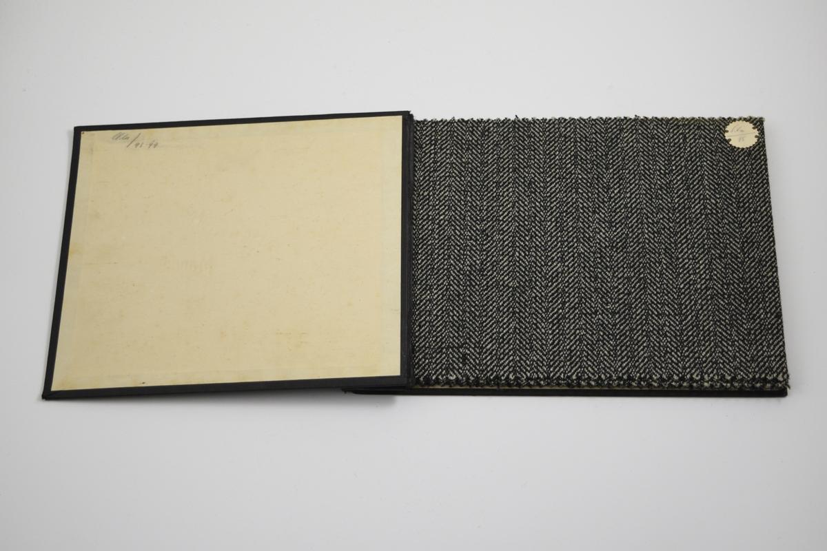 """Prøvebok med 4 prøver. Middels tykke stoff med fiskebensmønster og striper - mønsteret er tilnærmet likt på forsiden og baksiden av stoffet. Samme vevemønster på alle stoffprøvene i boken, men med ulike farger og kombinasjoner. Stoffene ligger brettet dobbelt i boken. Stoffene er merket med en rund papirlapp, festet til stoffet med metallstifter, hvor nummer er påført for hånd. Innskriften på innsiden av forsideomslaget viser at alle stoffene har kvaliteten """"Ola"""".   Stoff nr.: Ola/98, Ola/98B, Ola/99, Ola/99B."""