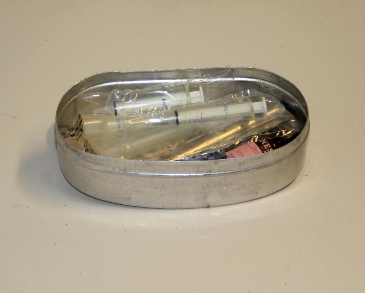 Oval aluminiumsboks med innhald. Innhald er div kanylar og sprøytar.