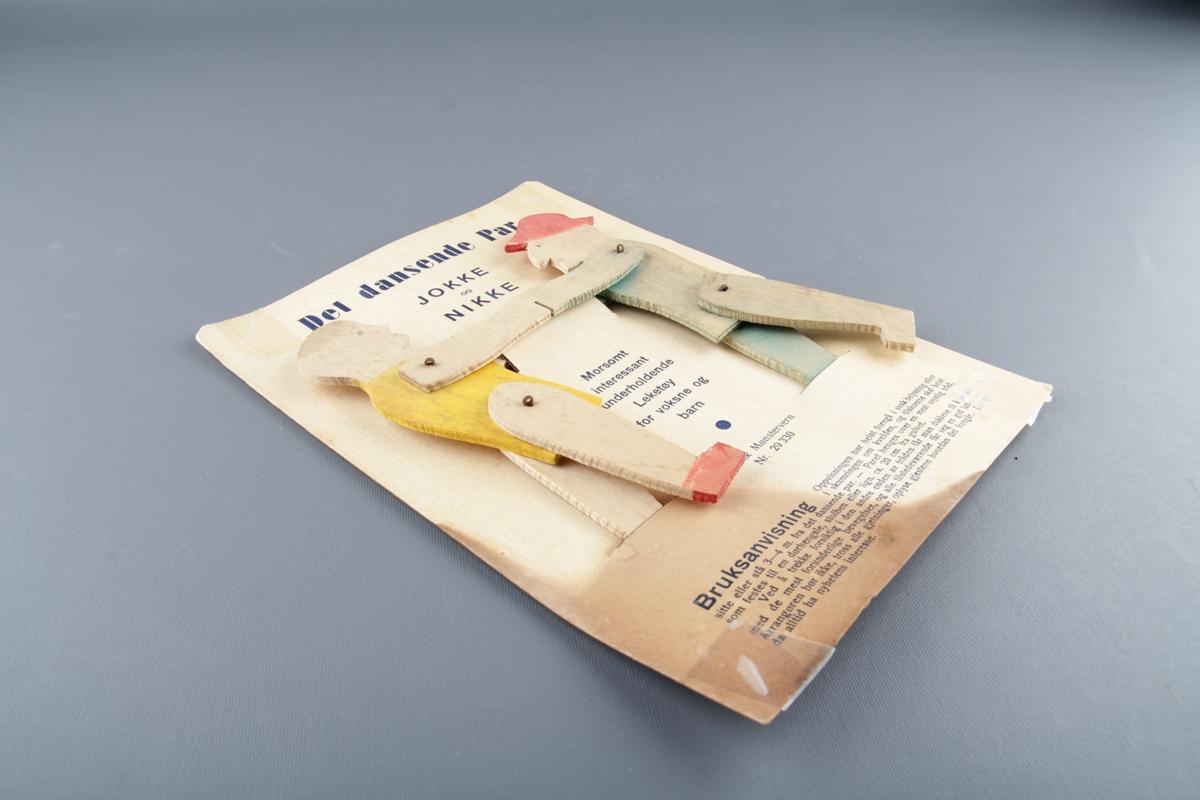 Mekanisk leketøy. Det er to tredukker som beveger seg om ein trekkjer i nokre snorer Festa på originalembalasjen - papp-plate med tekst, tittel og bruksanvisning.
