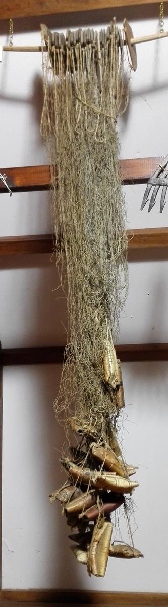 1 fiskegarn.  Ferskfiskgarn for örretfiske i Sogndalsvandet, bundet efter urgammel type av en kröbling paa Hyllekve. Nu meget defekt.  Gave fra G.F. Heiberg, Amble.