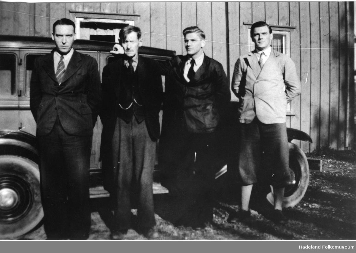 Fire herrer står oppstilt foran en bil.