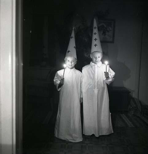 Med strut på huvudet och ljus i hand lussar två pojkar den 13 december 1951 i Glössbo. Pojkarna står i ett mörkt rum klädda som stjärngossar i vita lucialinnen.